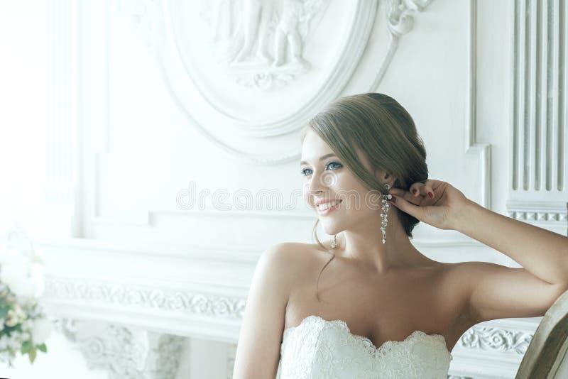 Sorriso feliz da noiva loura bonita nos raios de luz imagens de stock royalty free
