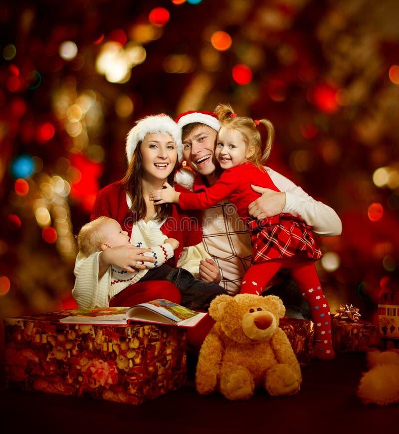 Sorriso feliz das pessoas da família de quatro pessoas do Natal sobre o backgrou vermelho fotografia de stock royalty free