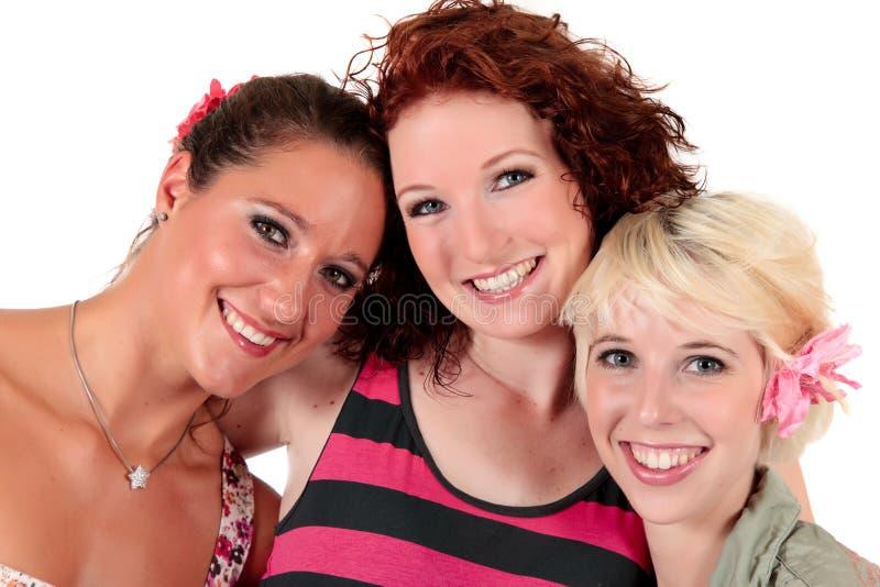 Sorriso feliz de três amigos das mulheres imagens de stock