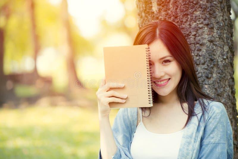 Sorriso feliz do escritor adolescente bonito da menina com o livro de nota do diário fotografia de stock
