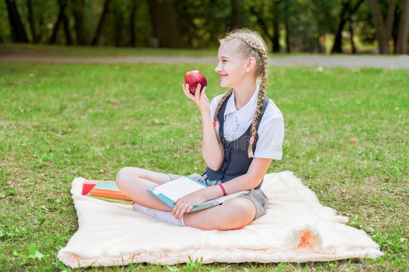Sorriso feliz do estudante com maçã à disposição estudante que senta-se em uma cobertura em um parque com livros de texto fotos de stock royalty free