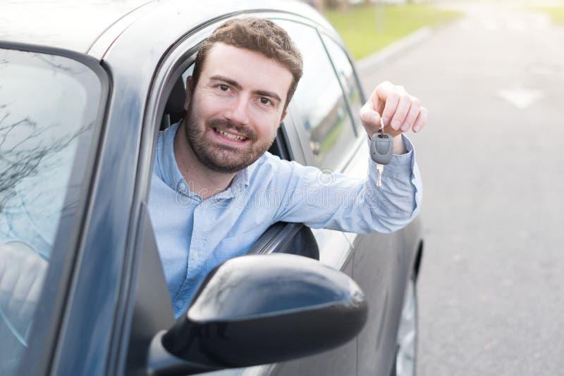 Sorriso feliz do homem assentado em seu carro que guarda a chave fotografia de stock