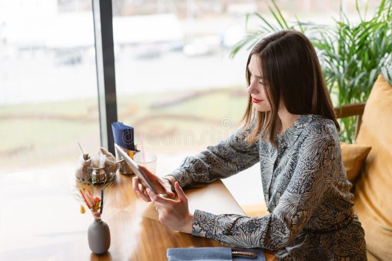 Sorriso femminile La giovane donna che scrive sulla compressa, chiacchierante, mantiene un blog Lavoro delle free lance nel cowor immagine stock