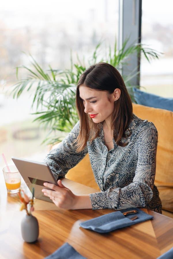 Sorriso femminile La giovane donna che scrive sulla compressa, chiacchierante, mantiene un blog Lavoro delle free lance nel cowor fotografia stock