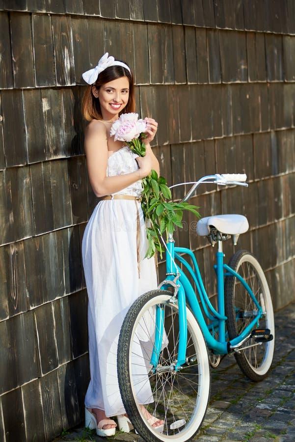 Sorriso levantamento consideravelmente fêmea perto da parede de madeira escura com peônias e a bicicleta azul fotos de stock royalty free