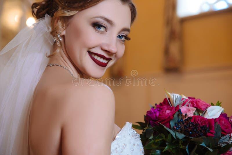 Sorriso modelo da vista próxima e mostrar fora seus dentes brancos bonitos Um ramalhete de rosas vermelhas vem ao bolo da menina fotografia de stock