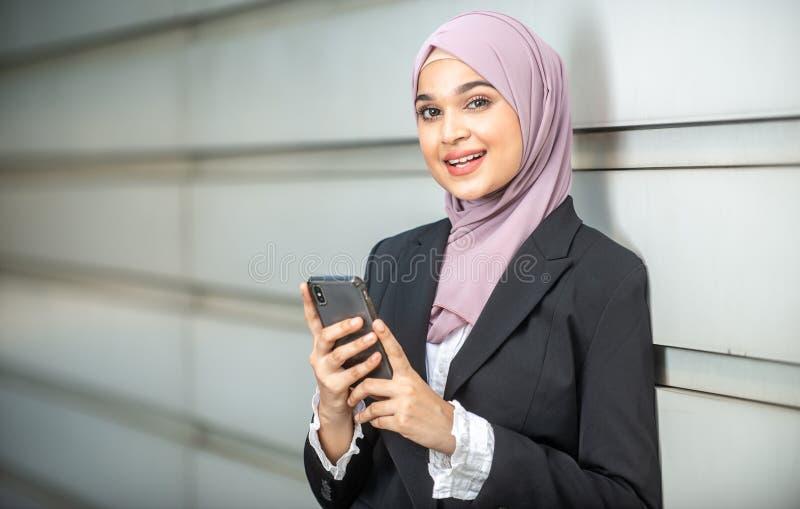 Sorriso muçulmano fêmea novo do empresário, guardando seu smartphone imagens de stock