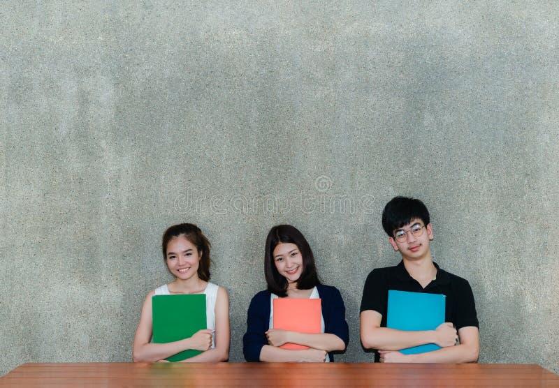 Sorriso novo do grupo de estudantes que abraça o livro dos dobradores da escola foto de stock