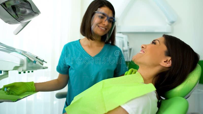 Sorriso paciente da senhora feliz no dentista após o procedimento, controle regular na clínica fotografia de stock royalty free