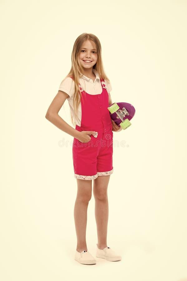 Sorriso pequeno da menina com a placa do patim isolada no branco Skater da criança que sorri com longboard Criança do skate no ro imagens de stock