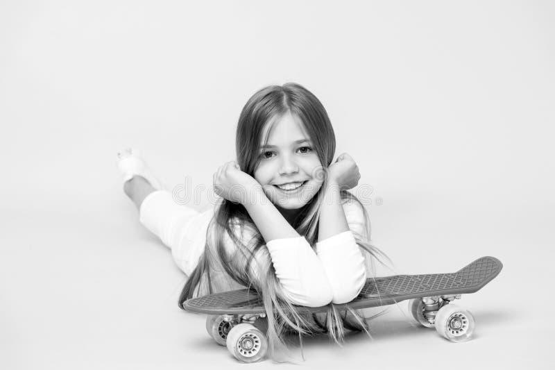 Sorriso pequeno da menina com placa do patim no fundo cor-de-rosa Skater da criança que sorri com longboard Mentira da criança do foto de stock royalty free