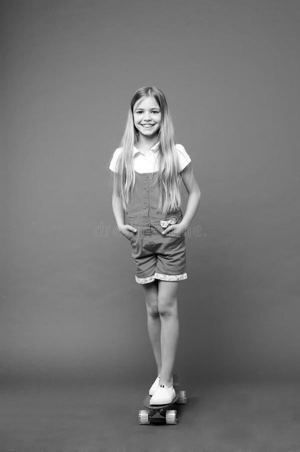 Sorriso pequeno da menina com placa do patim no fundo violeta Skater da criança com longboard Criança do skate no fato-macaco cor fotografia de stock royalty free