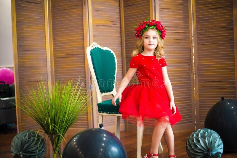 Sorriso pequeno da menina, forma Criança que sorri com penteado louro no vestido vermelho Conceito do sal?o de beleza Haircare, c fotografia de stock