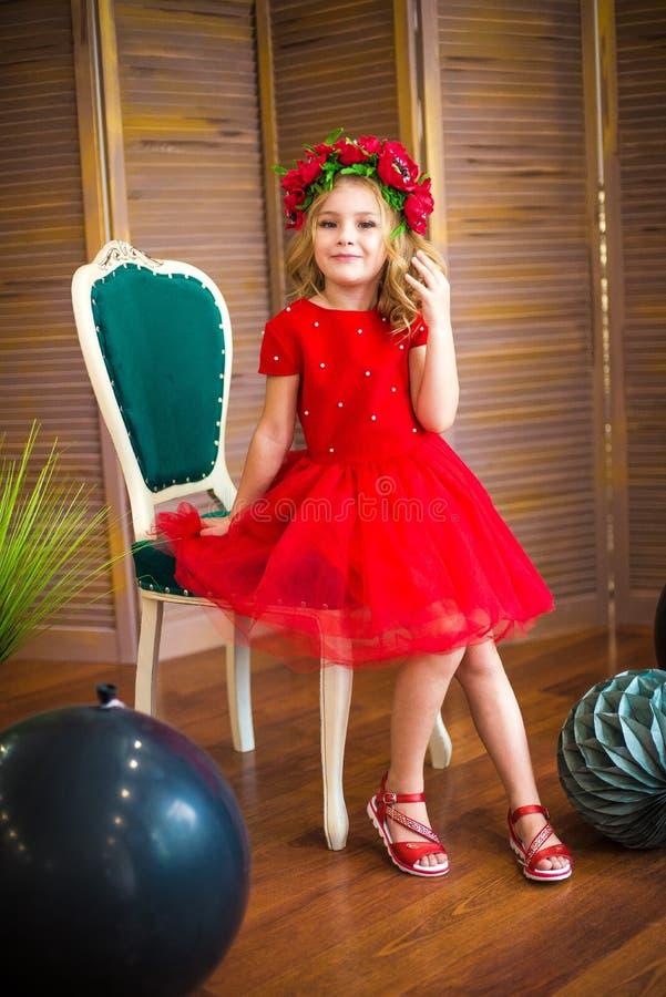 Sorriso pequeno da menina, forma Criança que sorri com penteado louro no vestido vermelho Conceito do sal?o de beleza Haircare, c fotografia de stock royalty free