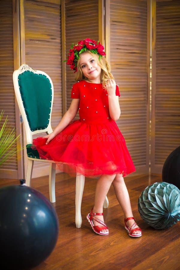 Sorriso pequeno da menina, forma Criança que sorri com penteado louro no vestido vermelho Conceito do sal?o de beleza Haircare, c foto de stock royalty free