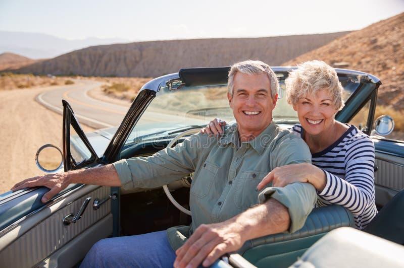 Sorriso senior alla macchina fotografica dall'automobile senza coperchio, fine delle coppie su fotografia stock