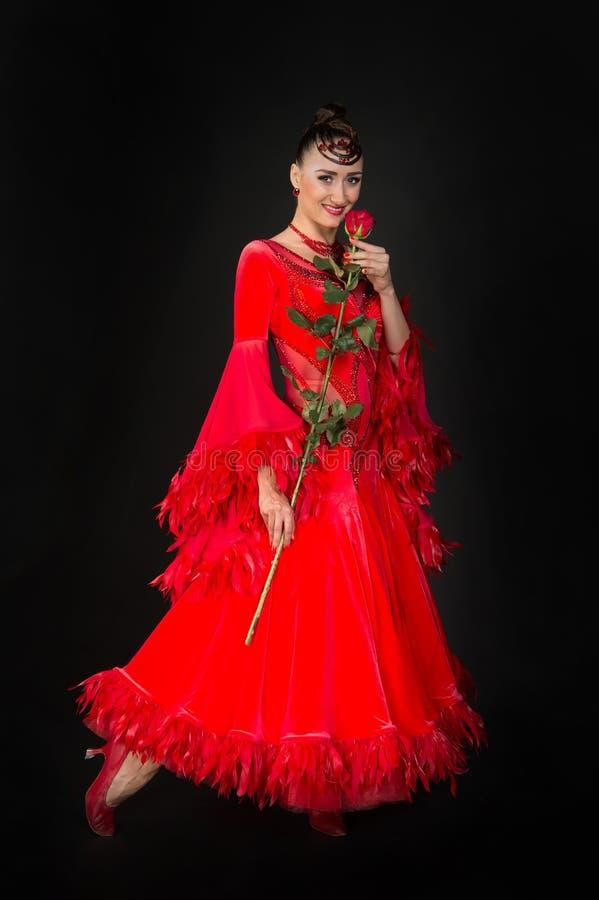 Sorriso sensuale della donna con il fiore rosa su fondo scuro immagini stock
