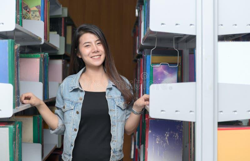 Sorriso sveglio dello studente con lo scaffale per libri in biblioteca, fotografia stock