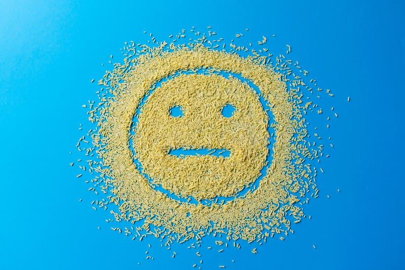 Sorriso triste di emoji su un fondo blu Smiley dai grani gialli dello zucchero immagini stock