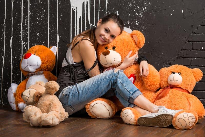 Sorriso urso consideravelmente à moda dos brinquedos dos abraços da jovem mulher fotos de stock royalty free
