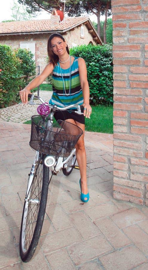 Sorrisos atrativos da mulher que sentam-se em uma bicicleta imagem de stock