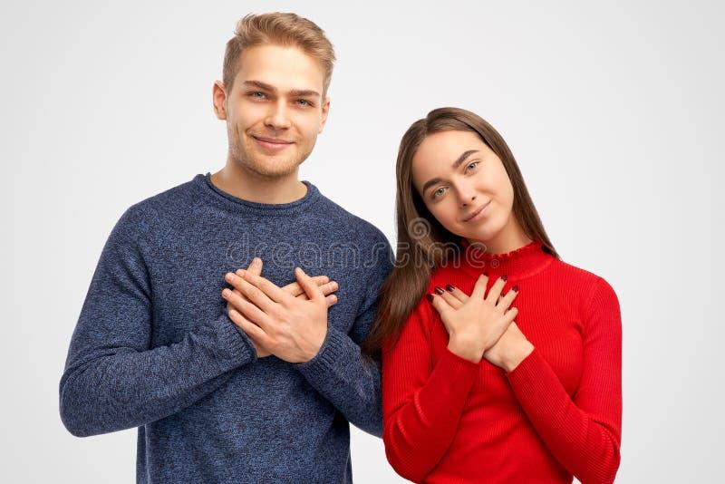 Sorrisos bonitos e olhares de um par na câmera, pondo suas palmas sobre a caixa perto do coração foto de stock
