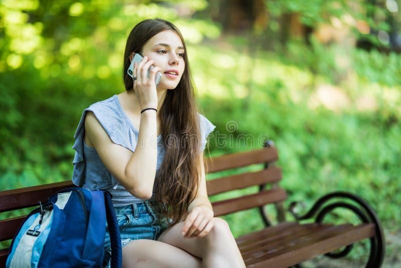 Sorrisos bonitos felizes da jovem mulher e fala no telefone no parque imagem de stock royalty free