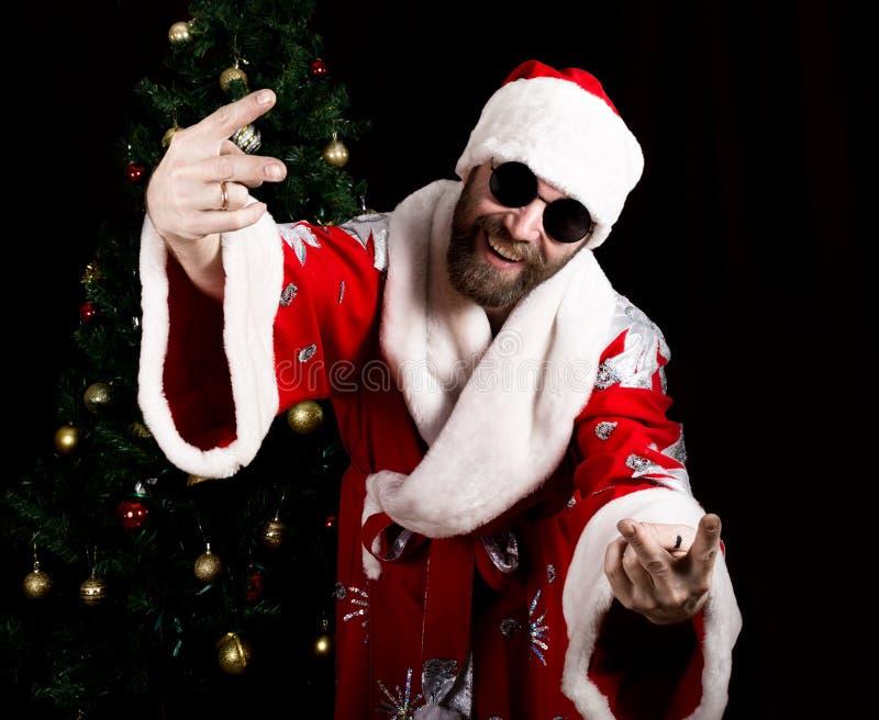 Sorrisos brutais maus de Santa Claus e mostrar o sinal do dedo no fundo da árvore de Natal foto de stock royalty free