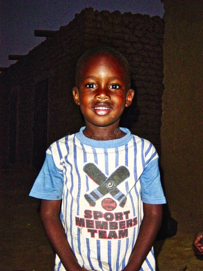 Sorrisos e poses malienses não identificados do menino na rua em Timbuktu As crianças de África sofrem da pobreza devido ao instá foto de stock royalty free