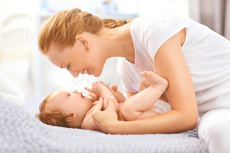 Sorrisos felizes da mãe no bebê que encontra-se na cama na sala fotografia de stock