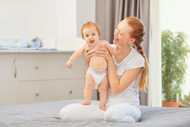 Sorrisos felizes da mãe no bebê que senta-se na cama na sala imagem de stock royalty free