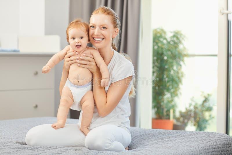 Sorrisos felizes da mãe no bebê que senta-se na cama na sala fotos de stock