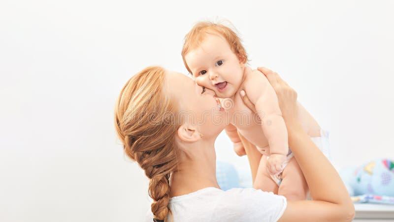 Sorrisos felizes da mãe no jogo do bebê na sala fotografia de stock