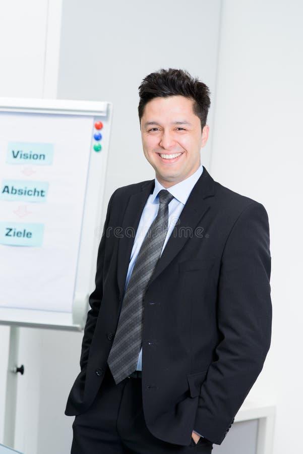 Sorrisos novos felizes do homem de negócios imagem de stock royalty free