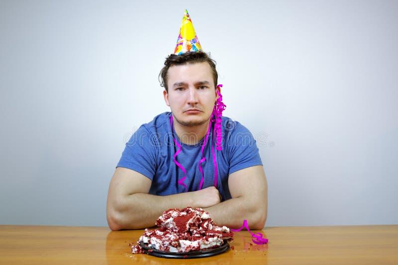 Sorrorful man med hatten för kotte för födelsedagparti på huvudet och att skrynkla kakan som gråter grabb i dåligt lynne, medan h fotografering för bildbyråer