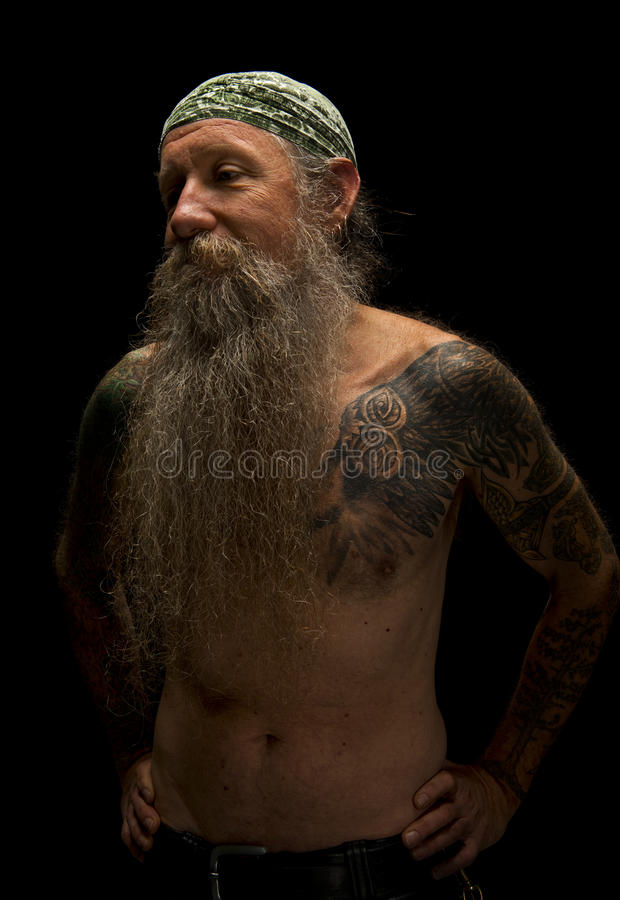 Sorrowful old man with long beard and hands on his hips royalty free stock images