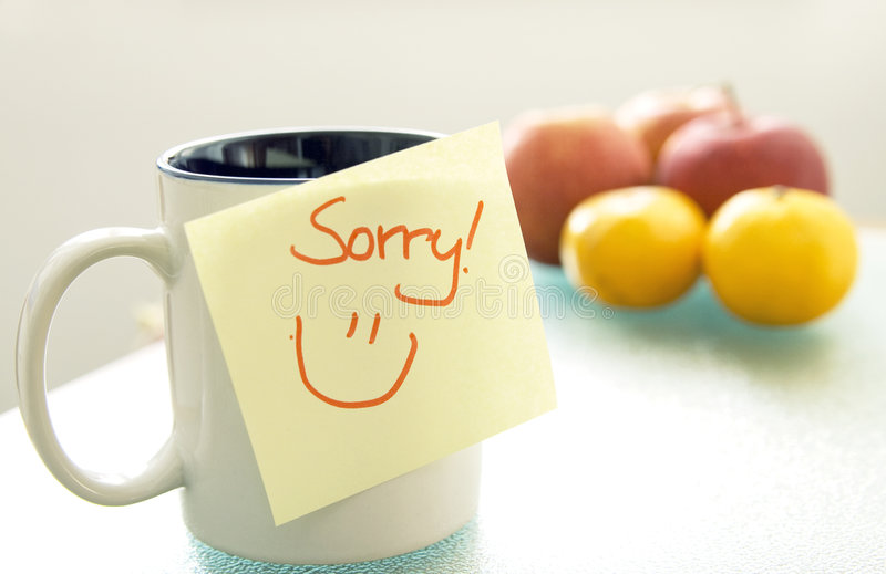 Sorry. Note saying sorry stuck on a cup, fruits in the background, shallow depth of field royalty free stock photo