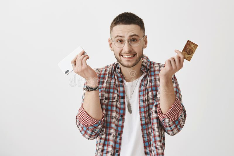 Sorry I spent all your money. Clumsy good-looking male shrugging and holding smartphone and credit card, feeling awkward. While smiling over gray background royalty free stock images