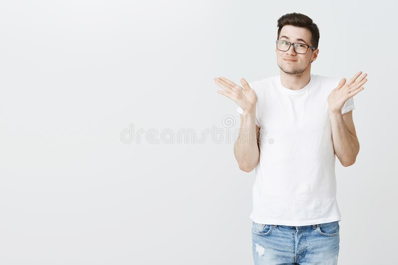 Sorry, my bad. Portrait of silly handsome young male model shrugging with raised palms near shoulders and light smirk. Appologizing making mistake or being royalty free stock photos