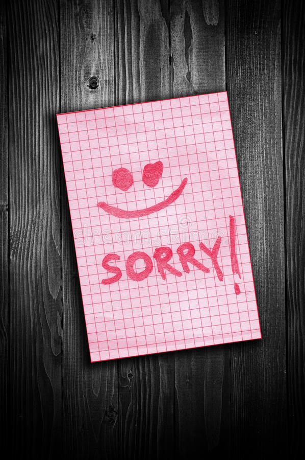 Sorry note. Sorry, handwritten reminder paper note over a wooden background royalty free stock photos