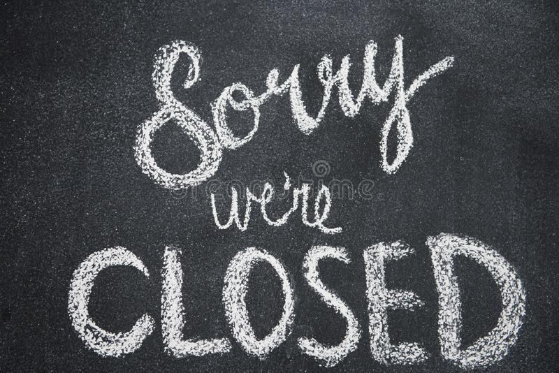 Sorry we`re closed. Is shown written in white chalk on a blackboard stock photography