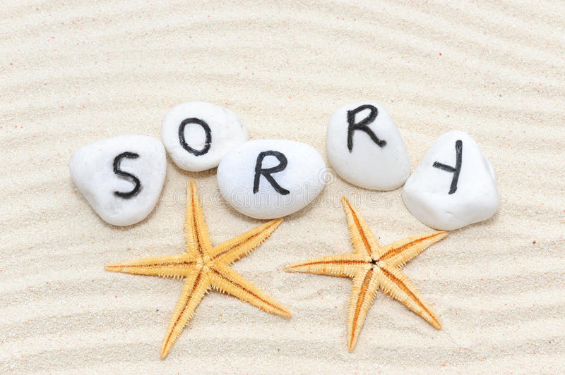 Sorry word. On group of stones with sand background stock photos