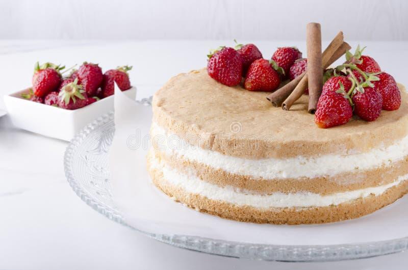 Sort av sockerkakan med smaklig kräm- och srawberry på exponeringsglasplattan arkivbild