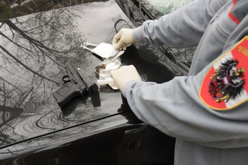 Sort de drogues saisies par la police autrichienne sur la table avec des armes photographie stock libre de droits