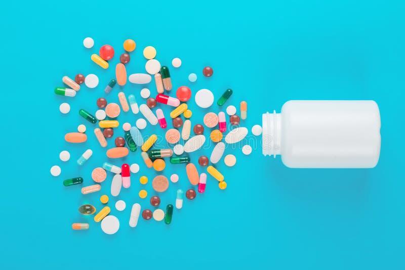 Sorterad farmaceutisk medicin färgade piller, minnestavlor och kapslar och flaskan på blå bakgrund arkivbilder