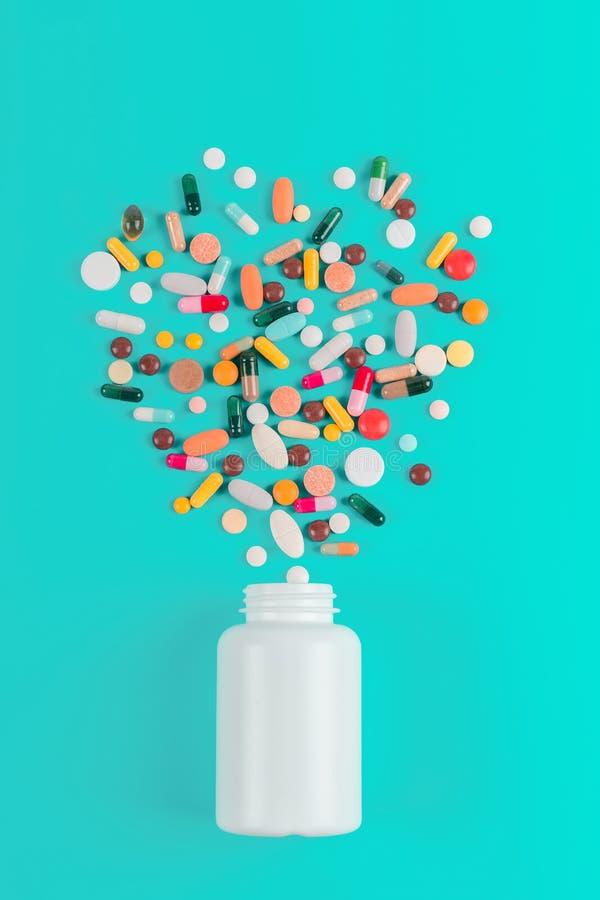 Sorterad farmaceutisk medicin färgade piller, minnestavlor och kapslar och flaskan på blå bakgrund arkivbild