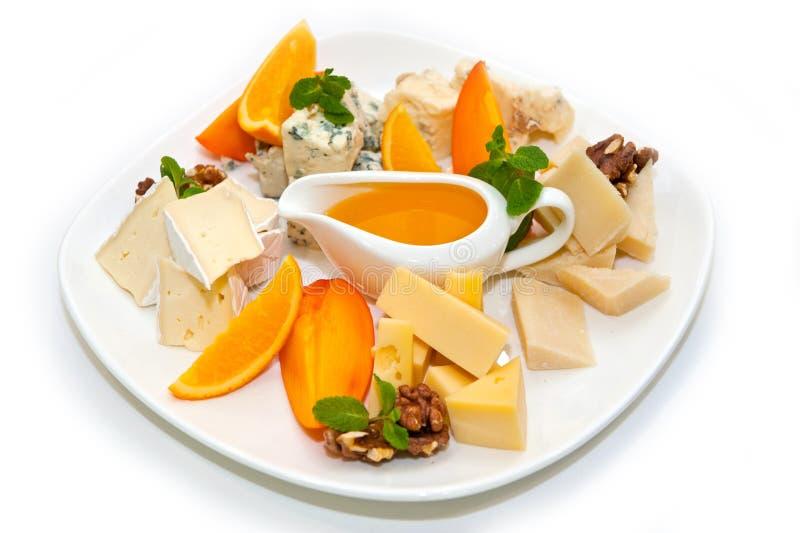 Sorterad ost med honung, valnötter, apelsinen och grapefrukten royaltyfri bild