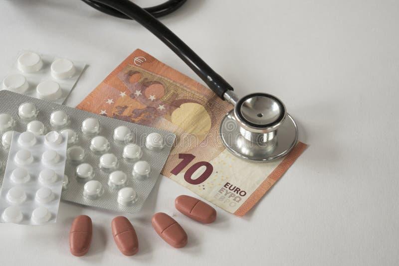Sorterade farmaceutiska medicinpiller, minnestavlor, stetoskop och pengar mot vit bakgrund royaltyfri fotografi