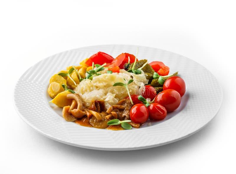 Sorterade inlagda grönsaker med surkålkål, peppar, gurkor, tomater, champinjoner på plattan som isoleras på vit bakgrund royaltyfri fotografi
