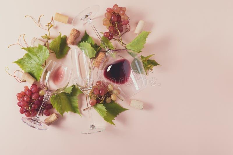 Sorterade vinglas med rött, rosa och vitt vin, druvan, sidor och kork som ligger på rosa bakgrund Vindegustationbegrepp royaltyfria bilder